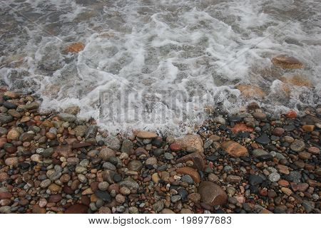 Waves rushing forward on a beach full of pebbles.  Pictured Rocks National Lakeshore, Upper Peninsula of Michigan