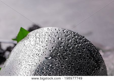 Closeup of a silver shaker with drops of water on a metallic smooth surface, leaves of fresh green mint, moisturized surface.