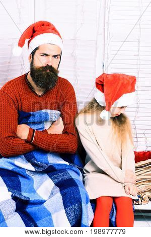 handsome bearded man in christmas red hat with blue checkered plaid blanket and cute blonde offended girl in beige dress with crossed hands on white studio background
