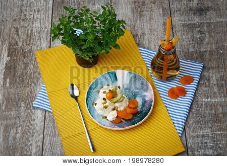 Top view of white sweet ice-cream with dried orange apricots, fresh juicy physalis, pumpkin seads, shining metallic tea spoon, little green tree, yellow and striped napkins , bottle with beverage on a wooden background.