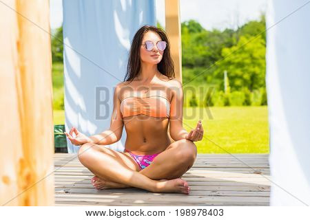 Attractive Young Woman In Yoga Poses In Bikini Lying On The Deck Chair Near The Pool .