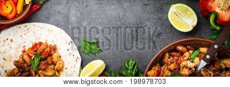Mexican taco with meat beans and vegetables at black stone table. Latin american food. Long banner format.