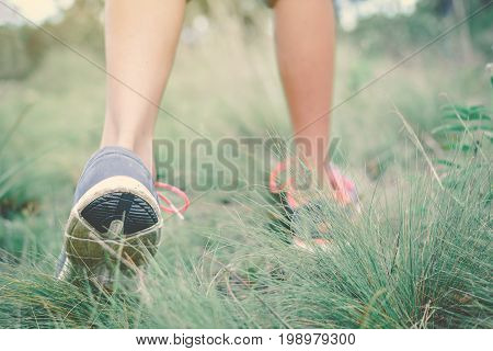 Feet of hipster girl walking in forest background Relax time on holiday