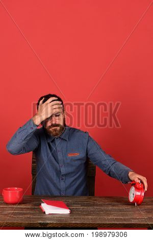 Man With Beard And Glasses Holds Alarm Clock, Red Background