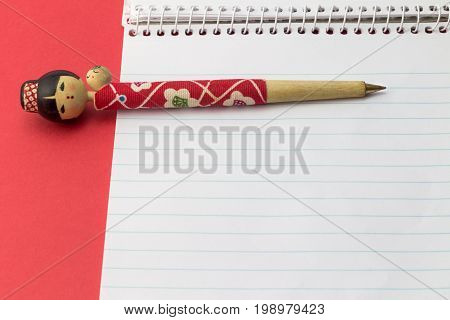 Figurine ball point pen on blank note pad with red background - Pen shaped as young Oriental woman with baby on back