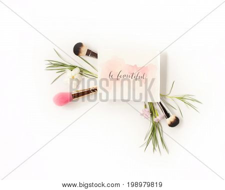 Top view of cosmetic brushes with green leaves and flowers and inspirational words written in calligraphy style `Be beautiful` on white. Beauty blog flat lay concept.