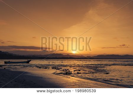 Silhouette of people swimming at the beach in Puerto Viejo de Talamanca Costa Rica at sunset