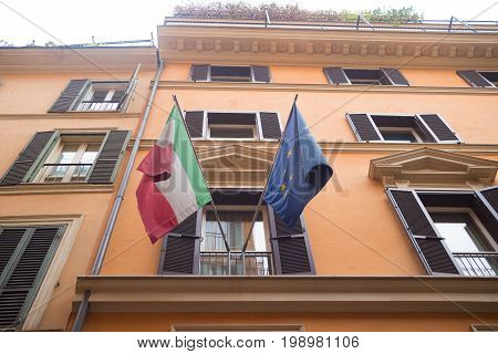 italian national flag and the european flag on a balcony in rome