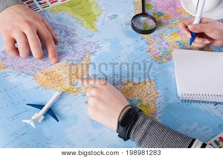 Couple planning airplane trip to USA, point on map, woman taking notes in blank notebook, copy space