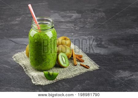 A close-up of a mason jar full of kiwi yogurt and natural ingredients on a gray background. Cool smoothie next to a group of exotic kiwis on a cream fabric. Summer beverage. Copy space.