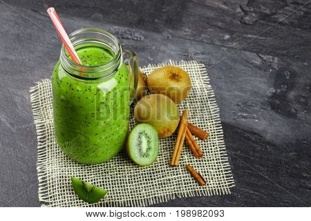 A view from above on a mason jar of kiwi yogurt and natural ingredients on a fabric on a black background. Decorative aromatic cinnamon next to a pile of kiwi fruits. Copy space.