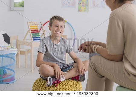 Boy Sitting On Yellow Pouf In Classroom
