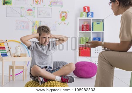 Kid Covering His Ears During Therapy