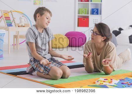 Kid Sitting On Floor Shrugging