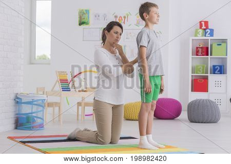 Physiotherapist Checking Back Of Boy At School