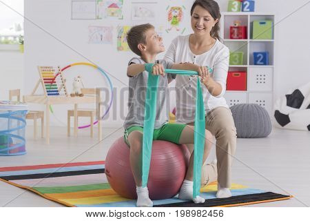 Physiotherapist Helping Boy Exercise On Ball