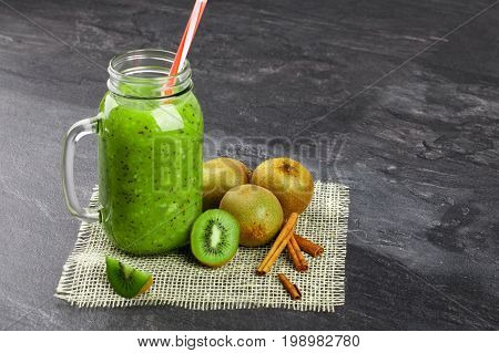 Close-up of a refreshing kiwi beverage gray stone background. A cocktail in a mason jar with a colorful straw. Colorful kiwis, cinnamon sticks and mint leaves next to a cool drink. Copy space.