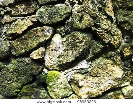 Mossy rough stone wall closeup photo texture. Rustic stone wall of ancient building. Green moss on stone closeup. Old masonry stonewall pattern. Empty wall closeup photo. Durability or safety concept.