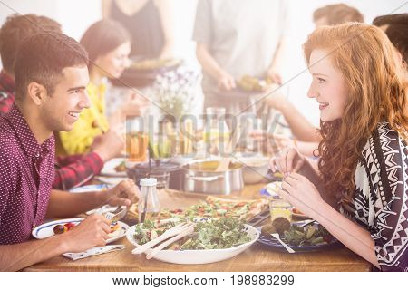 Handsome man enjoys tasty vegetarian meal with her red haired girlfriend in restaurant