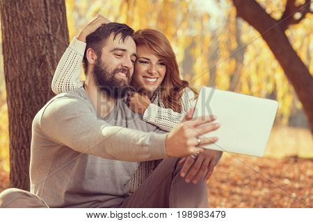 Couple in love sitting on autumn fallen leaves in a park surfing the net on a tablet computer in search for travel destinations. Focus on a guy