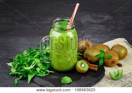 A close-up of a mason jar of kiwi juice and organic ingredients on a black table background. Decorative foliage and cinnamon sticks next to a heap of ripe kiwis. Copy space.
