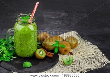 A close-up of a mason jar of kiwi yogurt and natural ingredients on a fabric on a black background. Green foliage and fresh mint next to a group of exotic kiwis. Copy space.