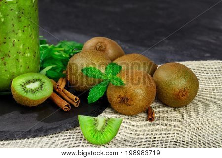 A close-up picture of light brown kiwi fruits with green peppermint and aromatic cinnamon on a table background. A cold kiwi milkshake in a glass jar next to natural fruits.