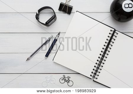 Education and work concept, top view shot of workplace. Stationery supplies - blank notepad, pen, binder clips, eight ball and smart watch on white wooden desktop, flat lay, copy space, mockup