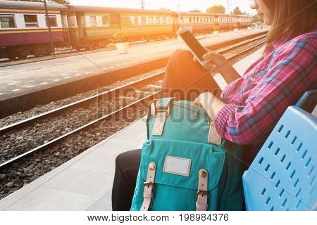 Young woman traveler and backpack waiting railway at train station, Young woman sitting with using smartphone at the train station, Summer holiday and travel concept, Sun light flare