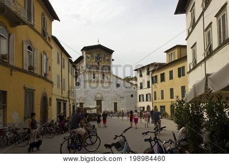 LUCCA, ITALY - AUGUST 15 2015: San Frediano square in Lucca city centre at day time with the famous Basilica and people around