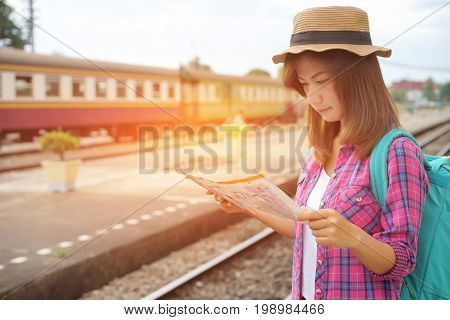 Young woman traveler with backpack and hat at the train station and looking on the map for plan to travel, Travel concept