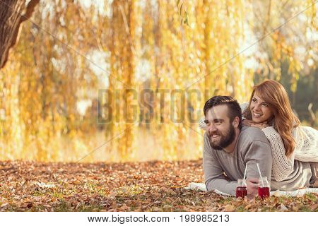 Young couple in love lying on a fallen autumn leaves under a tree in a park drinking an ice tea and enjoying a wonderful autumn day. Focus on a man