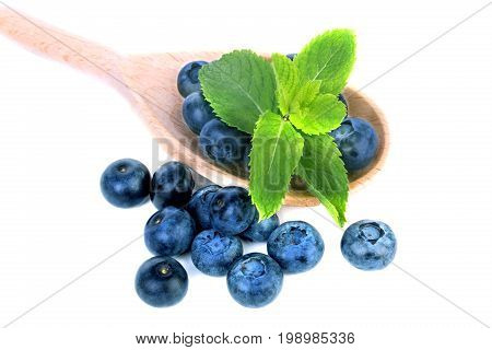 Close-up of a pile of sweet blueberries and green mint leaves in a wooden spoon, isolated on a white background. Some berries near the spoon with nutritious bilberries. Copy space.