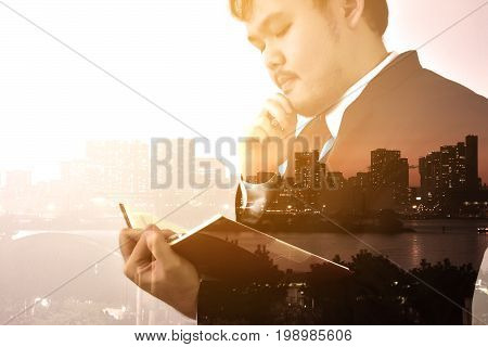 Businessman looking memo and Thinking for idea with big city or town in backgroundDouble exposure panoramic view contemporary megalopolis background orange sun light business concept