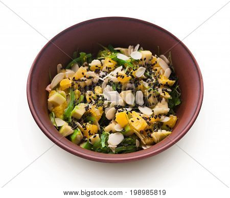 Healthy japanese restaurant food isolated at white. Bowl of avocado and orange salad with seaweed, almond flakes and black sesame. Asian fusion cuisine