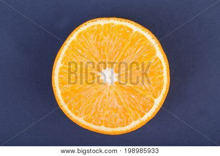 A view from above of a juicy, sweet and ripe cut orange fruit on a dark purple background. A round orange slice full of nutritious and healthy vitamins. Citrus fruit. Vitamin C.