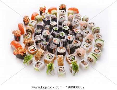 Big party sushi set isolated on white background. Japanese food delivery and take away. Fish and vegetable rolls, salmon nigiri and spicy gunkans