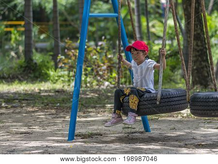 Asian little girl on swing in a playground. Clipping mask on child and swing
