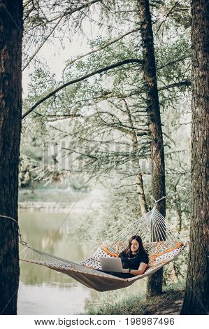 Beautiful Brunette Woman Relaxing On Hammock Outdoors Near Lake In The Forest, Freelancer Working In