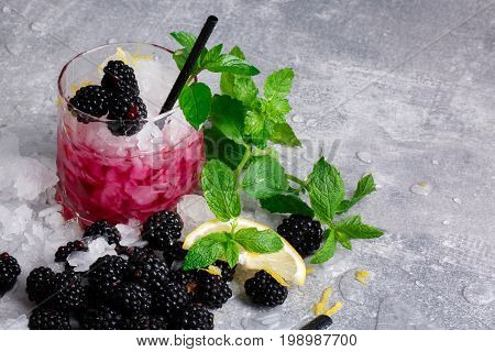 Refreshing drink with ice cubes, lemon, fresh green mint and sappy blackberries in a pink glass on a grey background. Copy space. Summer beverages.