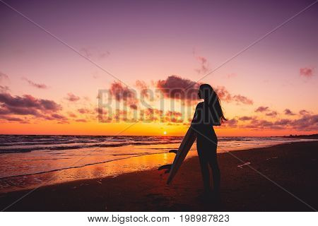 Silhouette of surfer girl on a beach at sunset. Surfer and ocean