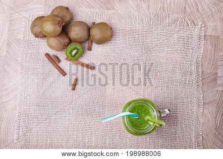 Top view of a mason jar full of kiwi smoothie with striped straw and a slice of green fresh kiwi on a white napkin on a light brown wooden background, cinnamon and kiwis on a wooden table, close-up.