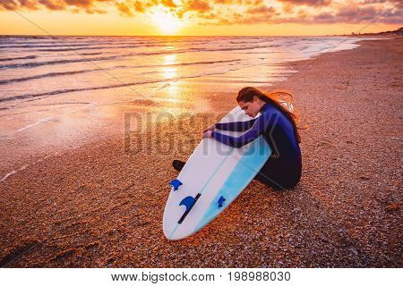 Surfer girl with surfboard on a beach at sunset or sunrise. Surfer and ocean