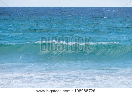 Background blur and powerful wave breaks along the shore