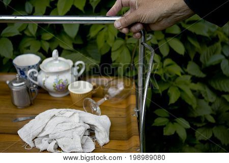 Waiter hand dragging uncleared serving table green foliage in the blurred background