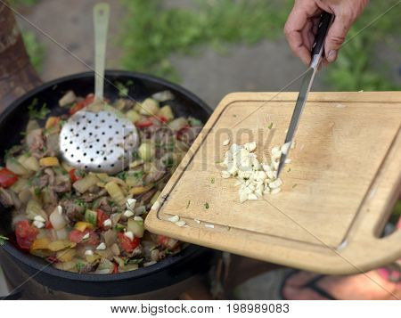 A cook hand adding chopped onion or garlic in nearly ready dish shallow depth of field closeup