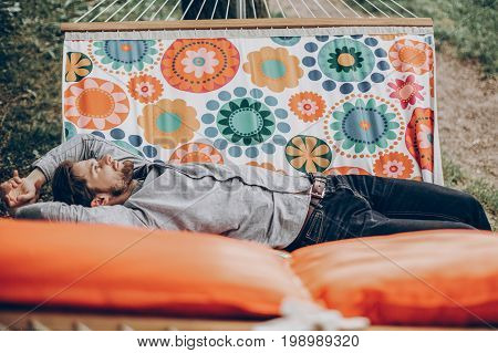 Handsome man relaxing on a hammock on a camping trip stylish hipster man lying on a hammock thinking and looking at the sky near a lake relaxation concept