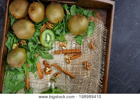 Top view of an exotic kiwi on a gray stone background. A colorful kiwis, nuts, cinnamon and leaves in a crate. Summer fruits on a wooden tray. Copy space.