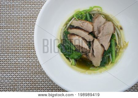 Delicious thai food bowl of instant noodle with steamed peking duck and soup on wooden background