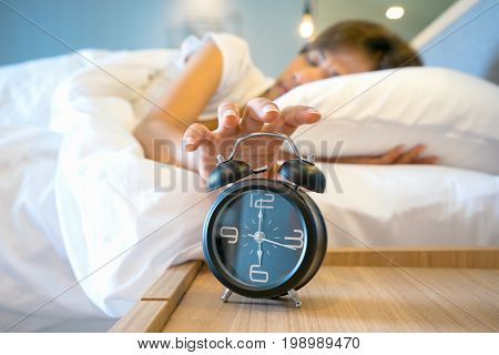 Sleepy young woman stretching hand to ringing alarm to turn it off, Early wake up, not getting enough sleep, getting work concept, Selective focus